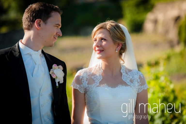 bride and groom smiling at each other as they walk through vineyards in front of stunning view of Lac Leman before luxury hotel Trois Couronnes, Vevey, Lake Geneva wedding by Gill Maheu Photography, photographe de mariage