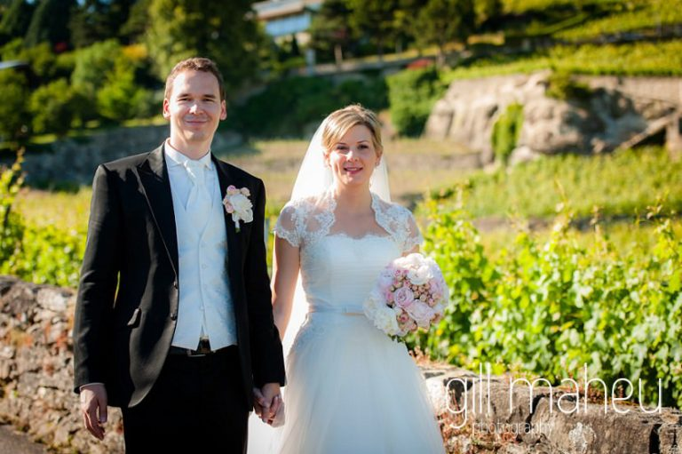 bride and groom smiling as they walk through vineyards in front of stunning view of Lac Leman before luxury hotel Trois Couronnes, Vevey, Lake Geneva wedding by Gill Maheu Photography, photographe de mariage
