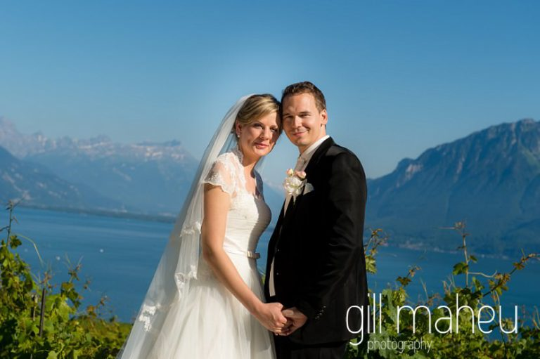 portrait of wedding couple head to head smiling at the camera in vineyards with stunning view of Lac Leman before luxury hotel Trois Couronnes, Vevey, Lake Geneva wedding by Gill Maheu Photography, photographe de mariage