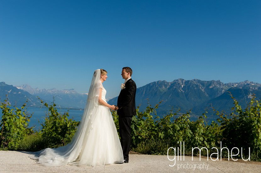 full length portrait of wedding couple in vineyards above Lac Leman before luxury hotel Trois Couronnes, Vevey, Lake Geneva wedding by Gill Maheu Photography, photographe de mariage