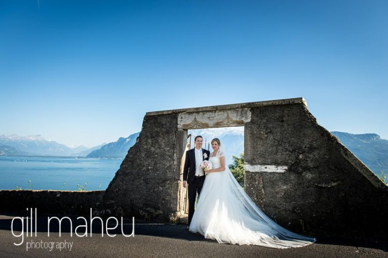 full length portrait of wedding couple in old stone arch stunning view of Lac Leman before luxury hotel Trois Couronnes, Vevey, Lake Geneva wedding by Gill Maheu Photography, photographe de mariage
