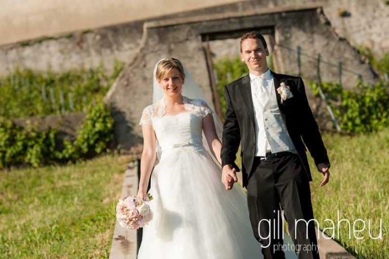 bride and groom smiling as they walk down the steps towards amazing view of Lac Leman before luxury hotel Trois Couronnes, Vevey, Lake Geneva wedding by Gill Maheu Photography, photographe de mariage