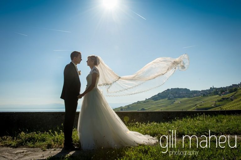 groom and his bride with floating veil silhouetted in front of amazing view of Lac Leman before luxury hotel Trois Couronnes, Vevey, Lake Geneva wedding by Gill Maheu Photography, photographe de mariage