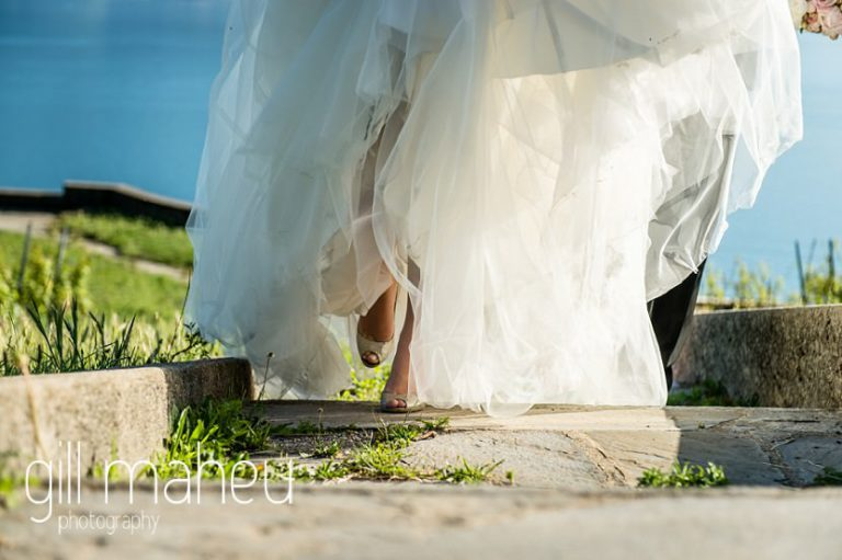 detailed shot of brides Jimmy Choo gold sparkly shoes peeping out from under Lusan Madongus wedding dress before luxury hotel Trois Couronnes, Vevey, Lake Geneva wedding by Gill Maheu Photography, photographe de mariage