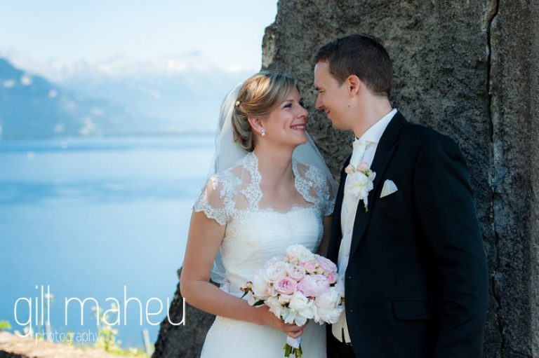 portrait of wedding couple talking to each other in old stone arch stunning view of Lac Leman before luxury hotel Trois Couronnes, Vevey, Lake Geneva wedding by Gill Maheu Photography, photographe de mariage