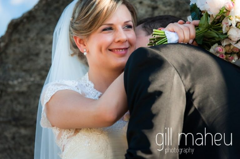 bride smiling over groom's shoulder before luxury hotel Trois Couronnes, Vevey, Lake Geneva wedding by Gill Maheu Photography, photographe de mariage