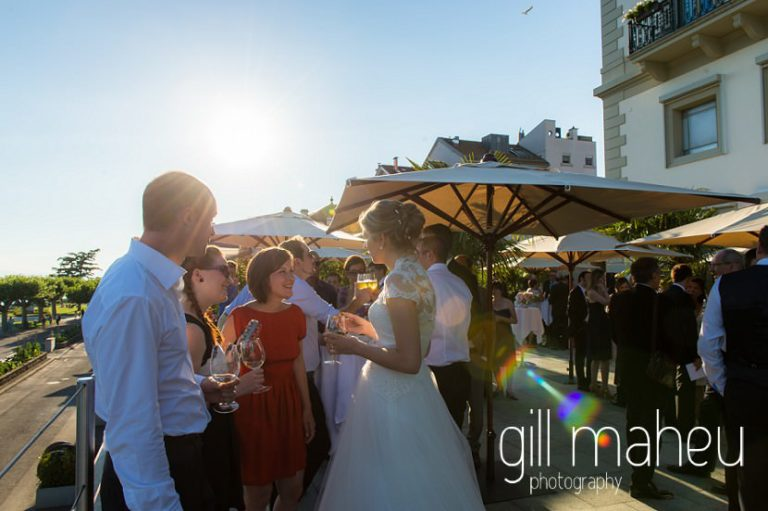 bride chatting with guests durig vin d'honneur wedding cocktail in the evening sunshine on the terrace of the luxury hotel Trois Couronnes, Vevey, Lake Geneva wedding by Gill Maheu Photography, photographe de mariage