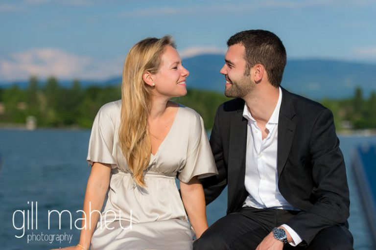 future bride and groom looking at each other in beautiful golden evening light on speed boat on  Lac Léman on Geneva engagement session by Gill Maheu Photography, photographe de mariage