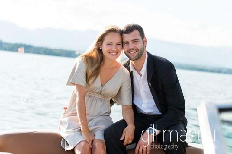 future bride and groom looking towards camera in beautiful golden evening light on speed boat on Lac Léman on Geneva engagement session by Gill Maheu Photography, photographe de mariage