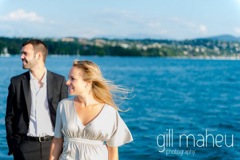 gorgeous couple looking into the sunset on Lac Léman with great dark storm clouds and golden light, Geneva engagement session by Gill Maheu Photography, photographe de mariage