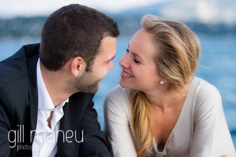 young couple chatting on speed boat on Lac Léman in golden light, Geneva engagement session by Gill Maheu Photography, photographe de mariage