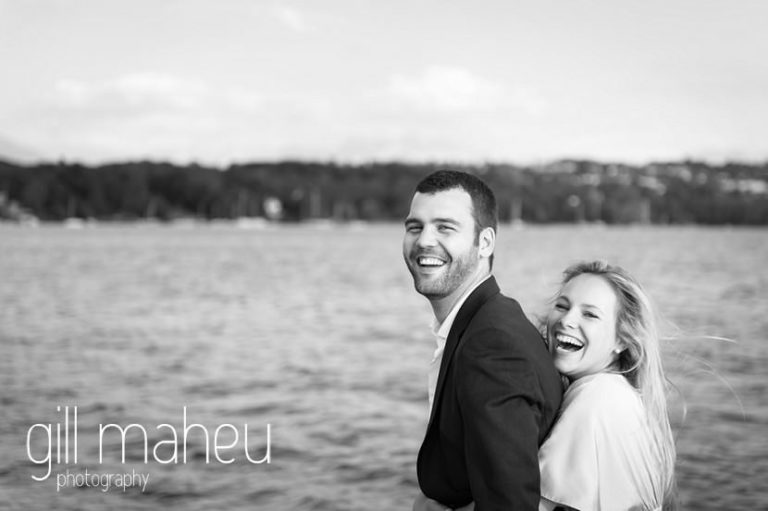 black and white of gorgeous couple laughing together on speed boat on Lac Léman, Geneva engagement session by Gill Maheu Photography, photographe de mariage