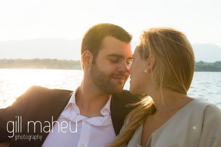 a romantic stolen moment style shot of gorgeous couple on speed boat on Lac Léman in golden light, Geneva engagement session by Gill Maheu Photography, photographe de mariage