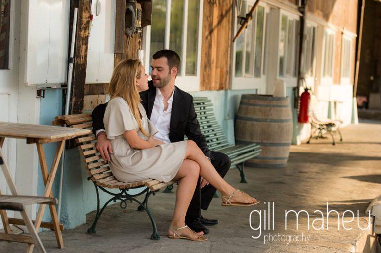 beautiful engaged couple sitting on bench at boathouse on the shore of on shore of Lac Léman, Geneva engagement session by Gill Maheu Photography, photographe de mariage
