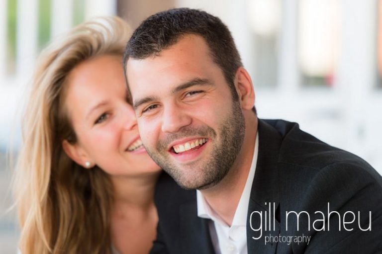close up of groom to be with bride to be behind him sitting on bench at boathouse on the shore of on shore of Lac Léman, Geneva engagement session by Gill Maheu Photography, photographe de mariage