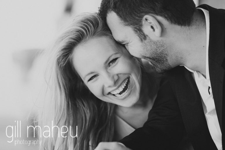 black and white photo of bride to be laughing with her groom sitting on bench at boathouse on the shore of on shore of Lac Léman, Geneva engagement session by Gill Maheu Photography, photographe de mariage