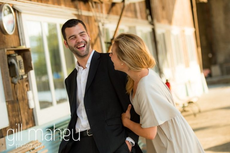 bride and groom laughing together in boathouse on the shore of on shore of Lac Léman, Geneva engagement session by Gill Maheu Photography, photographe de mariage