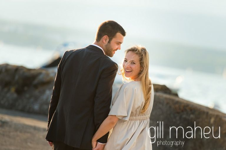 future bride and groom walking away from the camera towards the sunset on Lac Léman, Geneva engagement session by Gill Maheu Photography, photographe de mariage