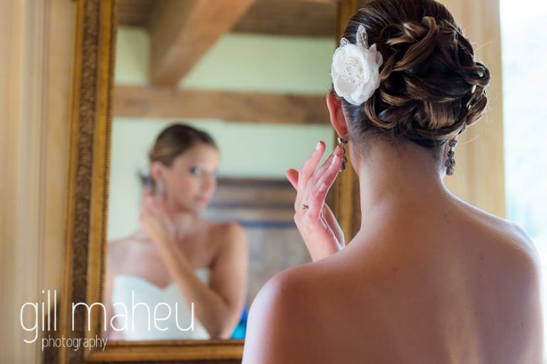beautiful bride putting in earrings in the suite nuptiale Jena Reno at Abbaye de Talloires, Annecy wedding by Gill Maheu Photography, photographe de mariage