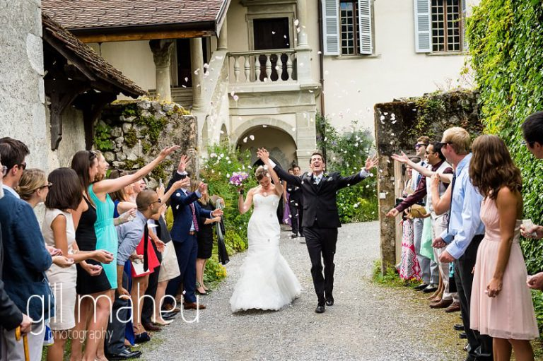 bride and groom leaving the wedding ceremony under rose petal confetti at Abbaye de Talloires, Annecy wedding by Gill Maheu Photography, photographe de mariage