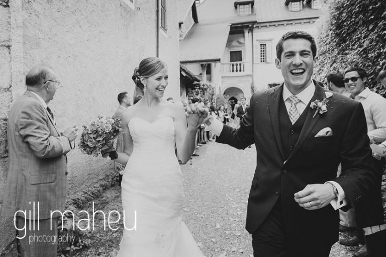 black and white of bride and groom laughing as they leave their wedding ceremony under rose petal confetti at Abbaye de Talloires, Annecy wedding by Gill Maheu Photography, photographe de mariage
