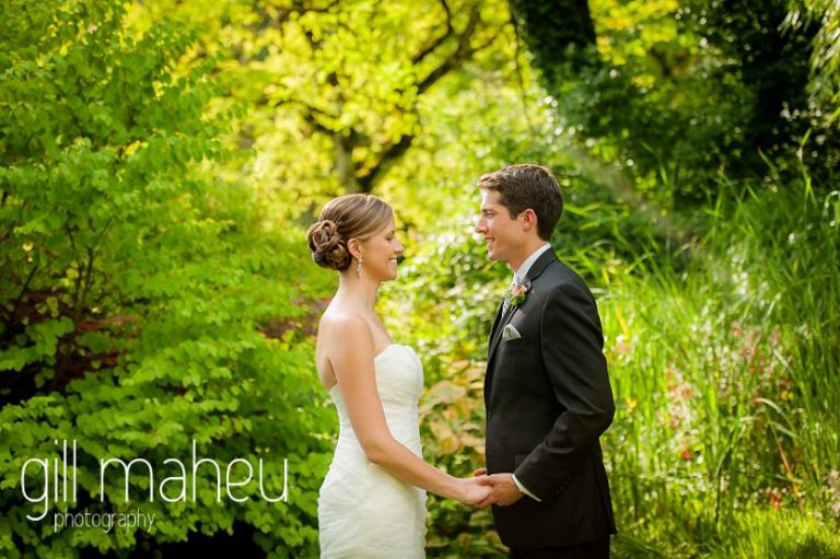 wedding couple holding hands with beautiful golden sunlit leaves behind them in portraits of the happy couple in the gardens of the Abbaye de Talloires, Annecy wedding by Gill Maheu Photography, photographe de mariage