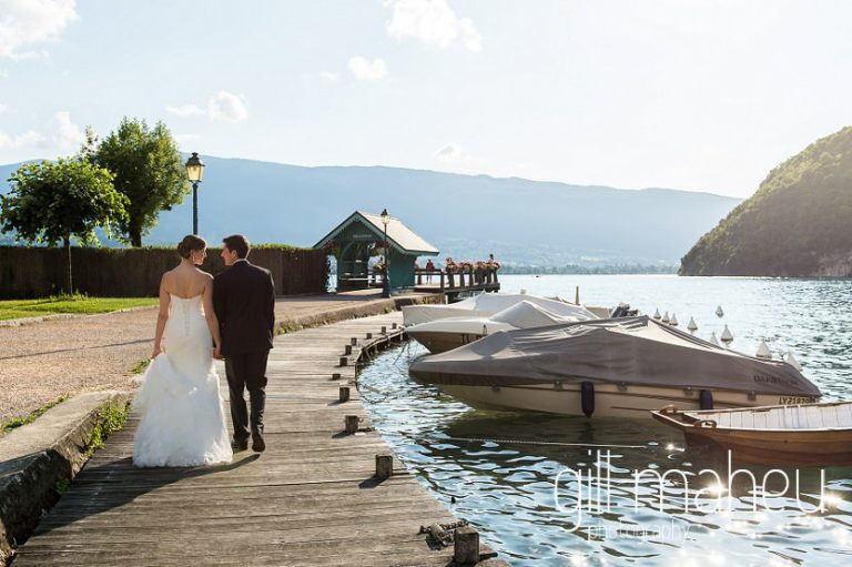 bride and groom walking away from the camera towards the ponton jetty in Talloires at their Abbaye de Talloires, Annecy wedding by Gill Maheu Photography, photographe de mariage
