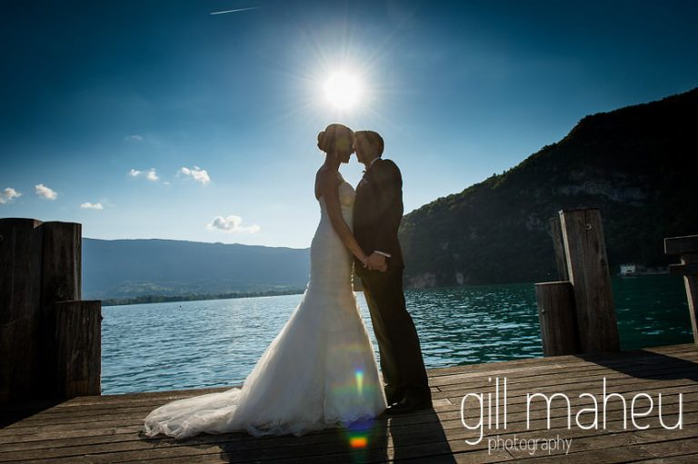 bride and groom kissing on the ponton jetty silhouetted against the evening sun on lac d'annecy at Abbaye de Talloires, Annecy wedding by Gill Maheu Photography, photographe de mariage