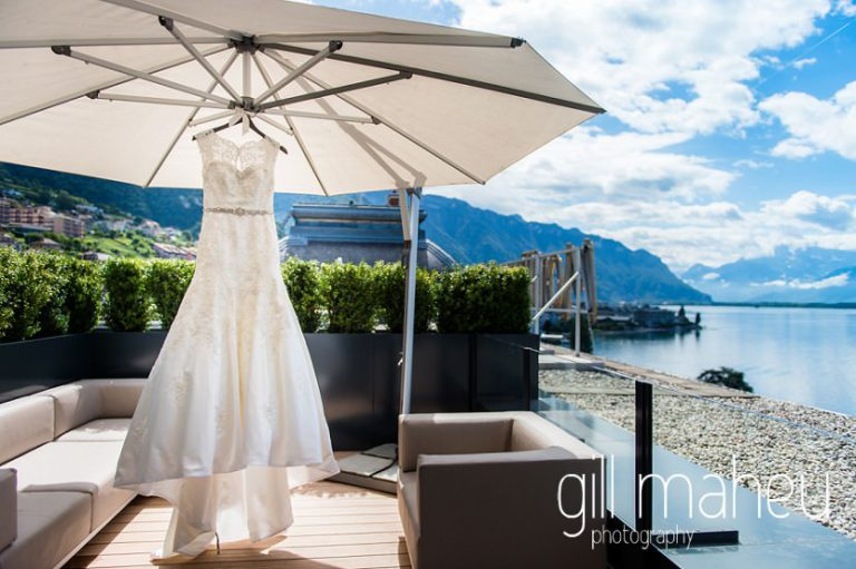 stunning wedding dress by David Tutera for Mon Cheri hanging from parasol on on the terrace at the Fairmont Le Montreux Palace, Lake Geneva wedding by Gill Maheu Photography, photographe de mariage