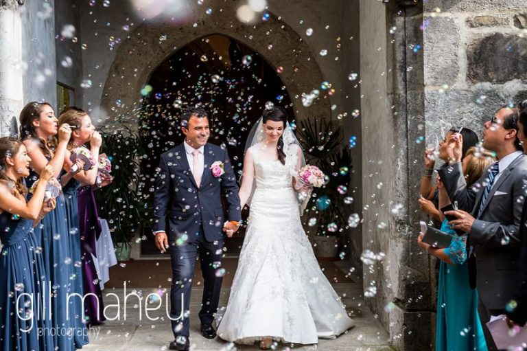 bride and groom leaving Eglise de Montreux under bubble confetti before  Fairmont Le Montreux Palace, Lake Geneva wedding by Gill Maheu Photography, photographe de mariage