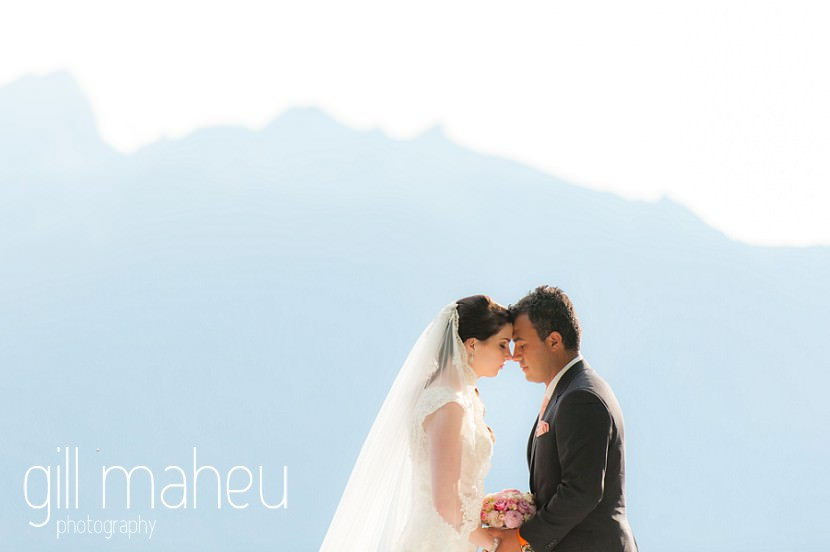 romantic portrait of bride and groom head to head silhouetted in front of blue mountains at Fairmont Le Montreux Palace, Lake Geneva wedding by Gill Maheu Photography, photographe de mariage