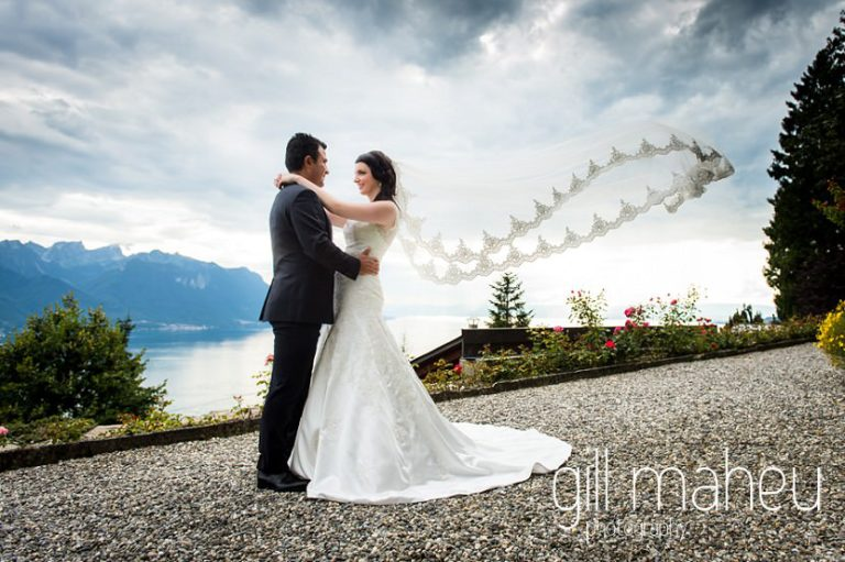 silhouetted shot of wedding couple and floating catherdral veil in front of stunning view down lac leman at Fairmont Le Montreux Palace, Lake Geneva wedding by Gill Maheu Photography, photographe de mariage