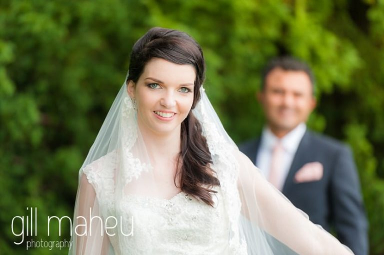 portrait of bride with groom in background at Fairmont Le Montreux Palace, Lake Geneva wedding by Gill Maheu Photography, photographe de mariage
