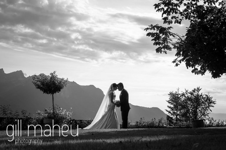 black and white photo of silhouetted shot of wedding couplein front of stunning view down lac leman at Fairmont Le Montreux Palace, Lake Geneva wedding by Gill Maheu Photography, photographe de mariage