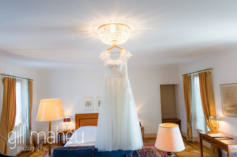 beautiful white Lilly wedding dress hanging from Chandelier at the Auberge du Raisin before Chateau de Glérolles, Lausanne, Lake Geneva wedding by Gill Maheu Photography, photographe de mariage