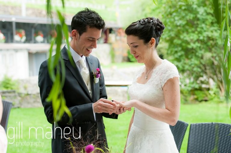 bride and groom exchanging rings in their outside ceremony at Chateau de Glérolles, Lausanne, Lake Geneva wedding by Gill Maheu Photography, photographe de mariage