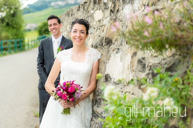 portrait of bride with groom in back ground by old stone wall in vineyards above lac léman at Chateau de Glérolles, Lausanne, Lake Geneva wedding by Gill Maheu Photography, photographe de mariage