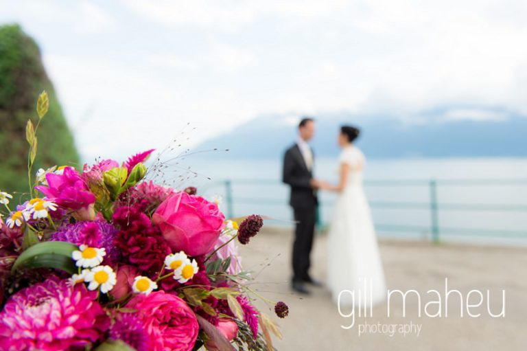 focus on brightly coloured bridal bouquet with wedding couple in background at Chateau de Glérolles, Lausanne, Lake Geneva wedding by Gill Maheu Photography, photographe de mariage