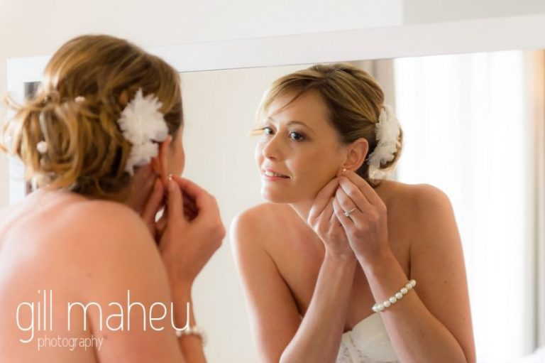 Bride putting in earring during bridal preparations at Hotel Pré Alpina before St Saphorin, Lake Geneva wedding by Gill Maheu Photography, photographe de mariage