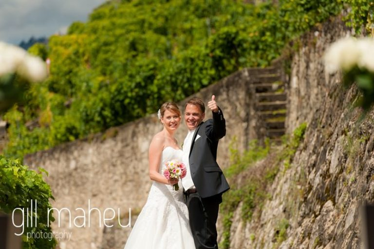 bride and groom giving a big thumps up to the camera at first look in the vineyards above Lutry at St Saphorin, Lake Geneva wedding by Gill Maheu Photography, photographe de mariage