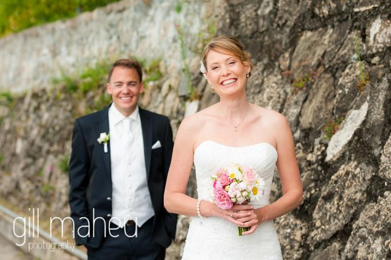 portrait of bride with groom in background at first look in the vineyards above Lutry at St Saphorin, Lake Geneva wedding by Gill Maheu Photography, photographe de mariage