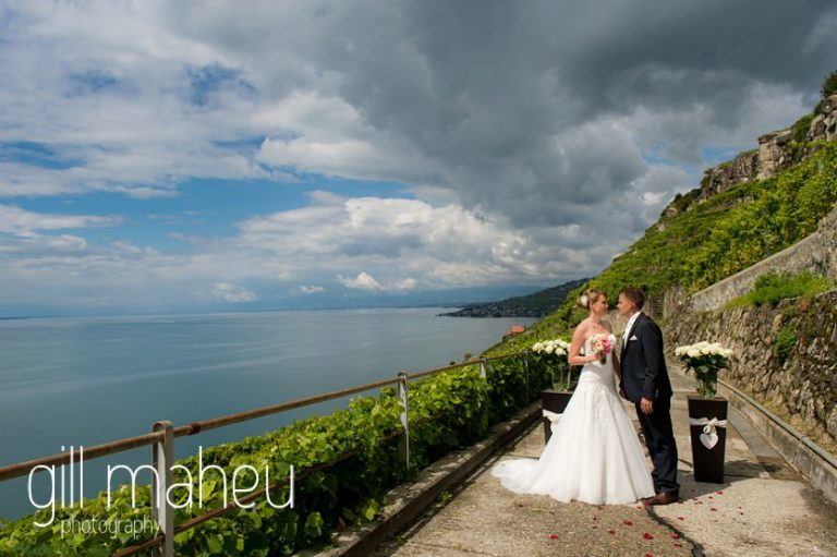 bride and groom embracing in front of stunning views of Lac Léman at first look in the vineyards above Lutry at St Saphorin, Lake Geneva wedding by Gill Maheu Photography, photographe de mariage