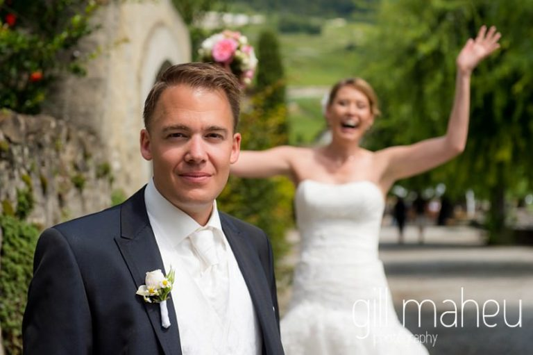 portrait of groom with bride celebrating in the background before St Saphorin, Lake Geneva wedding by Gill Maheu Photography, photographe de mariage