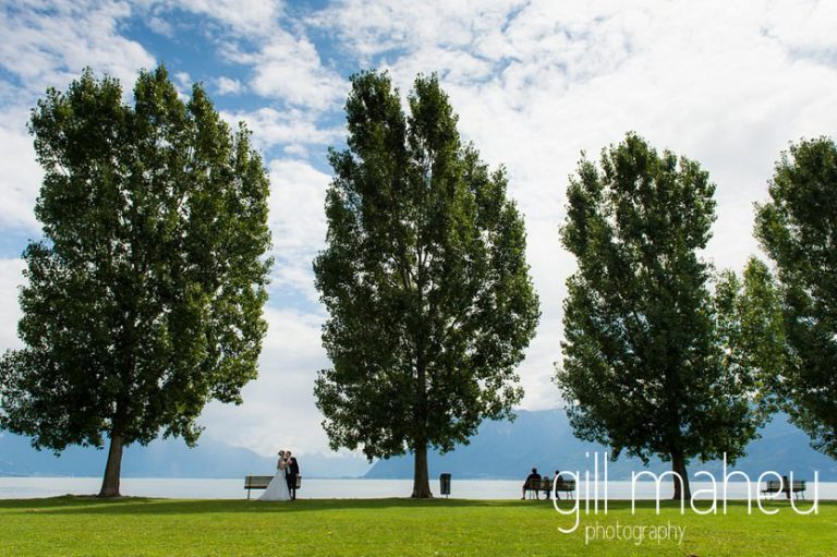 wide angle shot of bride and groom between the trees on the lakeside at Lutry for St Saphorin, Lake Geneva wedding by Gill Maheu Photography, photographe de mariage
