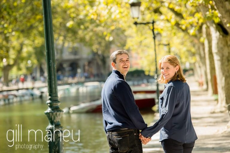 couple looking back at the camera as they walk along Le Paquier canal in lifestyle photo session in the Vielle Ville of Annecy by Gill Maheu Photography, photographe de mariage et de famille