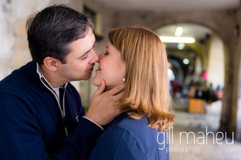 couple kissing under the arches in lifestyle photo session in the Vielle Ville of Annecy by Gill Maheu Photography, photographe de mariage et de famille