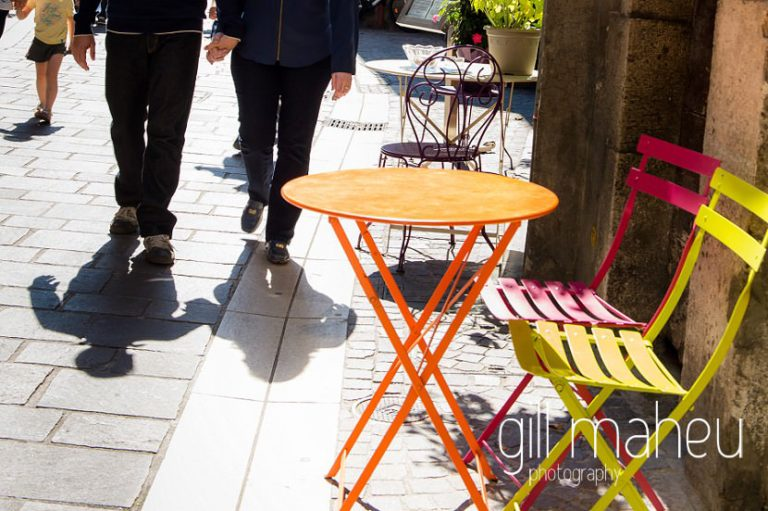 shadows of young couple walking past typical french fold up table and chairs on street in couple lifestyle photo session in the Vielle Ville of Annecy by Gill Maheu Photography, photographe de mariage et de famille