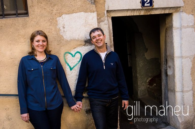 portrait of couple holding hands either side of blue heart graffiti on couple lifestyle photo session in the Vielle Ville of Annecy by Gill Maheu Photography, photographe de mariage et de famille