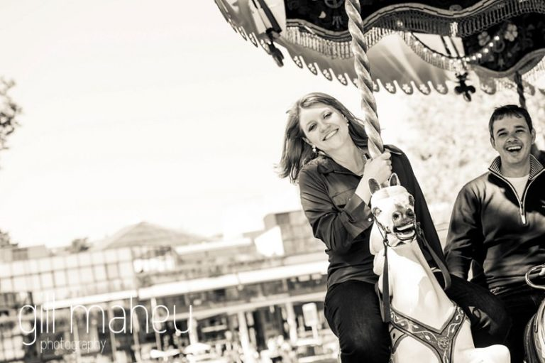 black and white portrait of young woman laughing on merry go round on Le Paquier in lifestyle photo session in the Vielle Ville of Annecy by Gill Maheu Photography, photographe de mariage et de famille