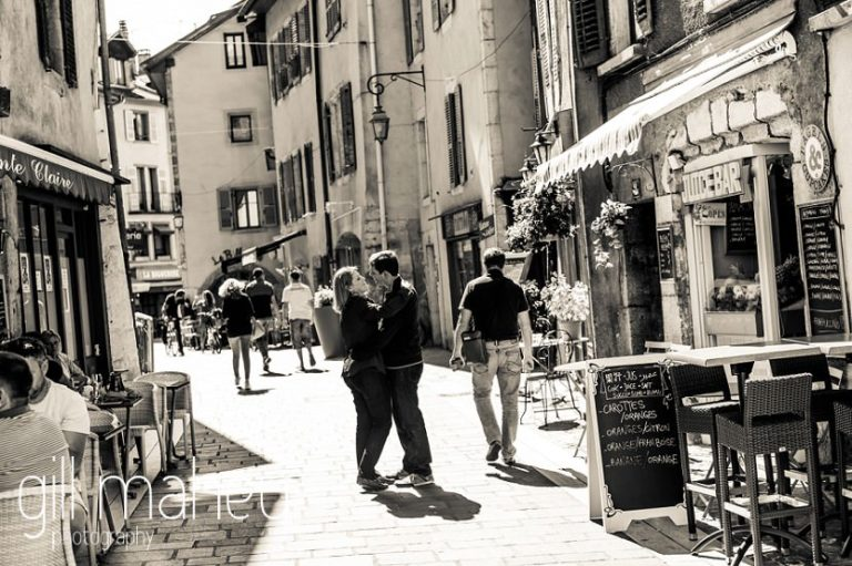 black and white of couple having fun in the streets in lifestyle photo session in the Vielle Ville of Annecy by Gill Maheu Photography, photographe de mariage et de famille